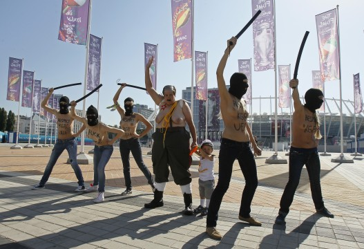 Activists from women's rights group Femen shout slogans in front of Olympic stadium in Kiev